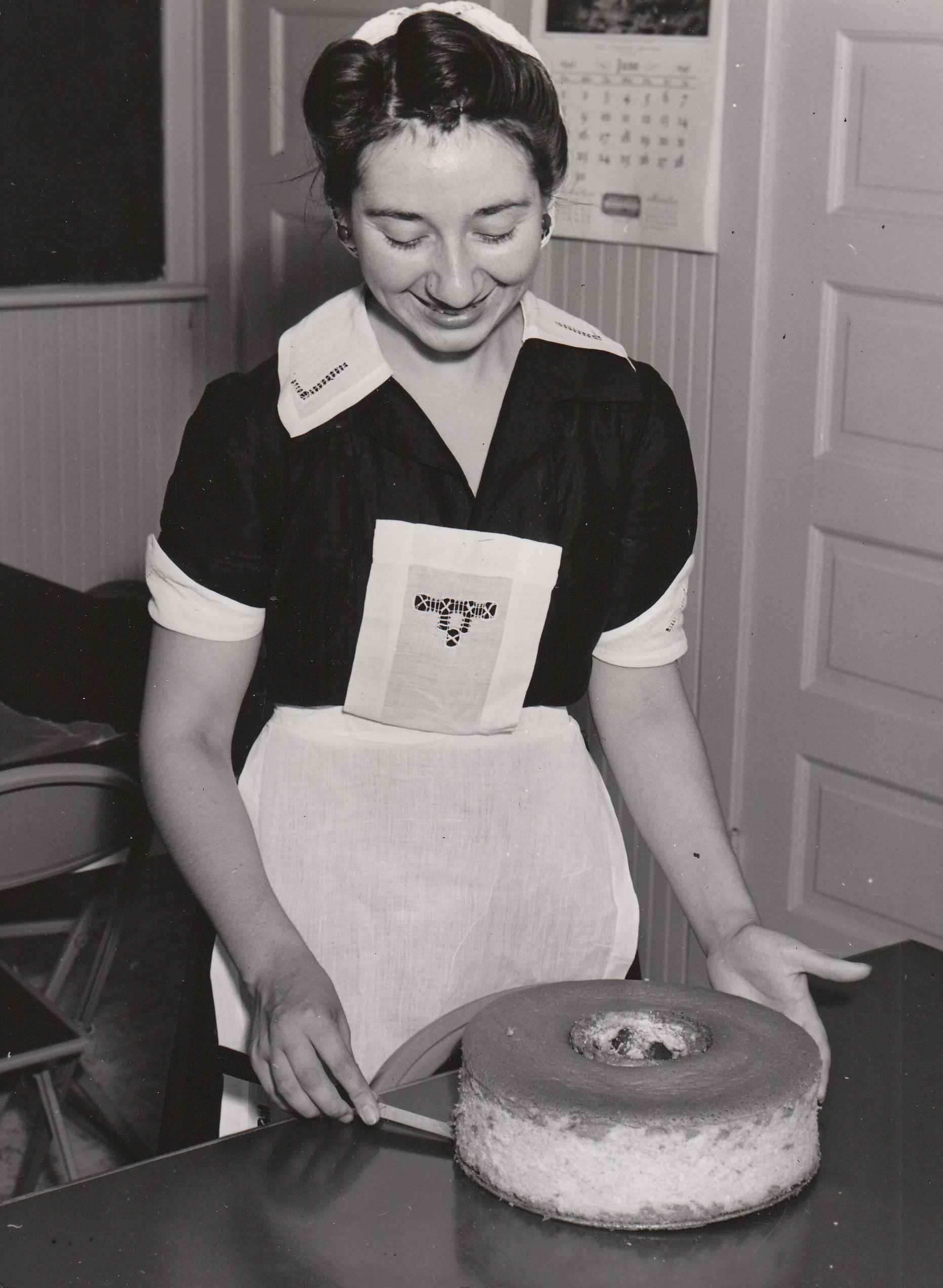 Binnie Mitchell, an NYA student worker at Pasadena Junior College (California), seems quite satisfied with her tempting creation. Photo courtesy of the National Archives (ca. 1935-1943).