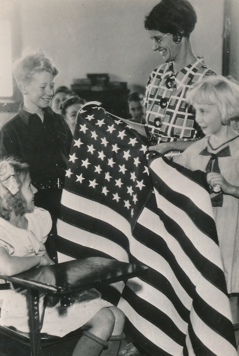 Teacher and students are both very pleased with an American flag sewn by WPA workers in Grand Rapids, Michigan. Photo courtesy of the National Archives (ca. 1935-1943).