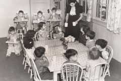NYA student worker Martha Garcia serves milk to children at the 28th St. School nursery, Los Angeles, California, January 30, 1941. Photo courtesy of the National Archives.