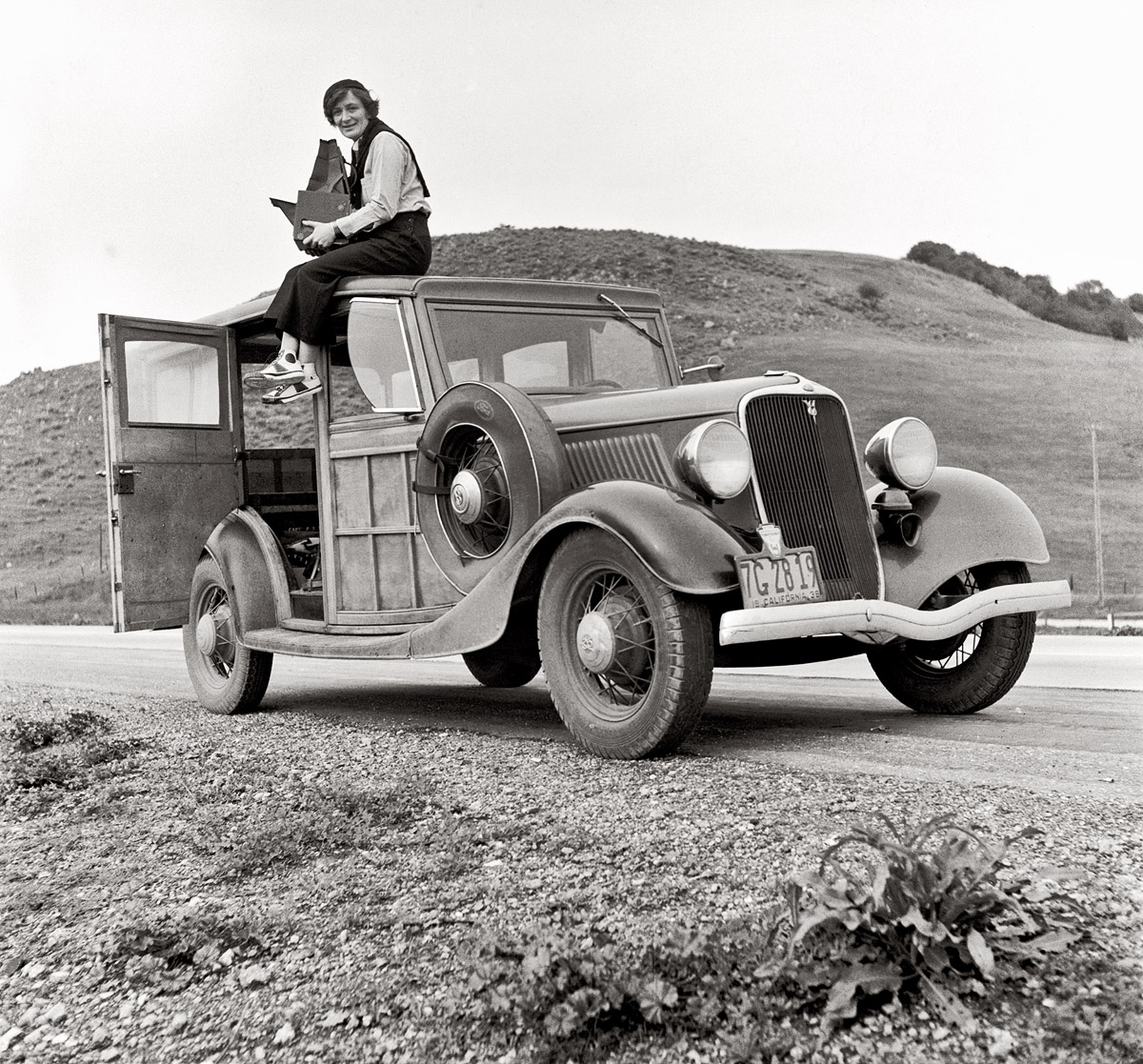 """From Shorpy.com: """"Dorothea Lange, Resettlement Administration photographer, in California atop car with her giant camera. February 1936. """""""