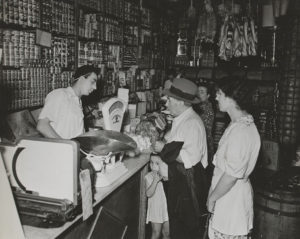 Waiting on customers in an Italian grocery store , Manhattan, 1937