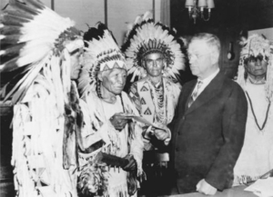 Secretary of the Interior Harold L. Ickes hands the first constitution issued under the Indian Reorganization Act to delegates of the Confederated Tribes of the Flathead Indian Reservation, Montana, 1935.
