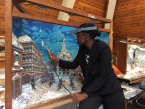 Restoration. Kiera Hammond works on the diorama of the Boston Massacre death of Crispus Attucks.